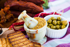 Fenugreek in porcelain dishes. Meat delicacies, olives, red pepp Stock Photos