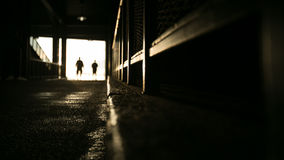 Fenway Ramp. Two people can be seen silhouetted in a white light at the top of a ramp inside of Fenway Park Stock Photos