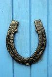 Fer à cheval noir cloué à la porte bleue Photos stock