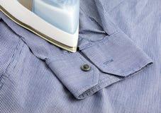 Fer de vapeur sur la chemise bleue photos stock