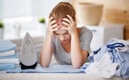 Fer repassant de vêtements de femme au foyer fatiguée de femme dans la blanchisserie photographie stock