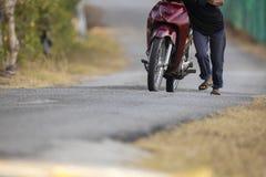 Feralny mężczyzna pcha naprzód nieżywego motocykl zdjęcie royalty free