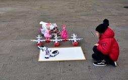 Feria de la Navidad de la ciudad Una niña con una capa roja y un sombrero negro mira los juguetes en el La Coruna, España de la c fotos de archivo