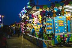 Feria del condado en la noche, juegos en la mitad del camino centraa Imagen de archivo