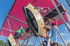 Feria holandesa con los niños desconocidos en un oscilación de madera Fotografía de archivo