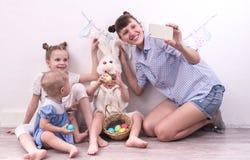 Feriado da família: A mãe com crianças comemora a Páscoa e faz o selfie no smartphone foto de stock