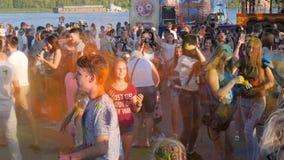 Feriado de pinturas coloridas, do pó brilhante no cabelo e da roupa da juventude feliz à rua, multidão de jovens filme