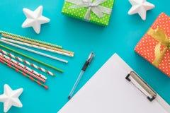 Feriado do Natal e do ano novo para fazer a lista com bloco de notas, pena, caixas de presente, tubos do cocktail, estrelas no fu Fotografia de Stock