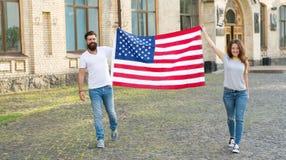 Feriado nacional O moderno e a menina comemoram 4o julho Povos patrióticos americanos Bandeira americana dos EUA dos pares patrio imagem de stock royalty free