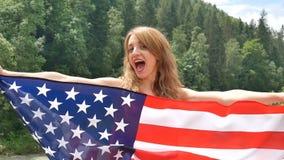 Feriado patri?tico Mulher emocional feliz com a bandeira americana no fundo verde da floresta durante o dia de verão fora EUA filme