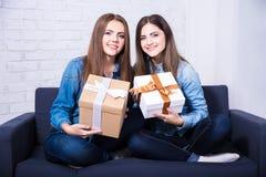 Feriados e amizade - meninas com as caixas de presente que sentam-se no sofá Foto de Stock