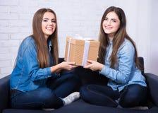 Feriados e amizade - meninas felizes com a caixa de presente que senta-se em s Fotos de Stock