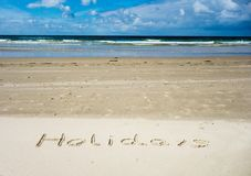 Feriados escritos na areia com o mar no fundo e no céu azul fotografia de stock royalty free
