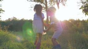 Feriados rurais, rapaz pequeno e menina pequena circundando e saltando guardando as mãos no por do sol video estoque