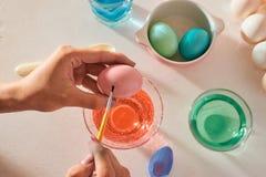 Feriados, tradição e conceito dos povos - fim acima das mãos do homem que colorem ovos da páscoa com escova imagem de stock royalty free