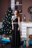 Ferie-, beröm- och folkbegrepp - ung kvinna i elegant klänning över julinrebakgrund royaltyfri foto