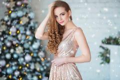 Ferie-, beröm- och folkbegrepp - ung kvinna i elegant klänning över julinrebakgrund royaltyfri bild