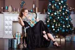 Ferie-, beröm- och folkbegrepp - ung kvinna i elegant klänning över julinrebakgrund royaltyfria bilder