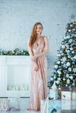 Ferie-, beröm- och folkbegrepp - ung kvinna i elegant klänning över julinrebakgrund Bild med royaltyfri fotografi