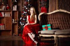 Ferie-, beröm- och folkbegrepp - ung le kvinna i elegant röd klänning över julinrebakgrund royaltyfria bilder
