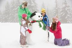 ferie för byggnadsbarngruppen skidar snowmanen fotografering för bildbyråer