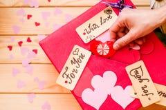 Ferie för dag för valentin` s röd ask för valentin med pappers- hjärtor valentinmeddelanden och gåvakort den kvinnliga handen med Royaltyfria Bilder