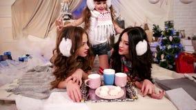 Ferie för det lyckliga nya året av unga flickor som ligger på säng, tycker om systrar familjvintersemester i varm hemtrevlig atmo arkivfilmer