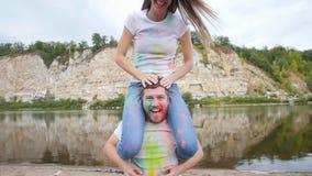 Ferie-, holi- och folkbegrepp - lyckligt par som har gyckel att täckas i holimålarfärgpulver arkivfilmer