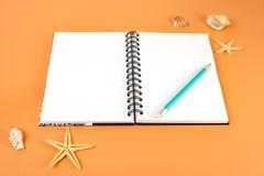 Ferie-, lopp- och sommarbegrepp - anteckningsbok med blyertspennan och skal på orange bakgrund arkivfoto