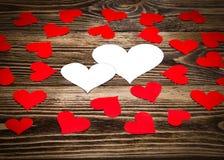 Ferie/romantiker/bröllop-/valentindagbakgrund med små pappers- röda hjärtor och meddelandekort i form av två hjärtor Royaltyfria Bilder