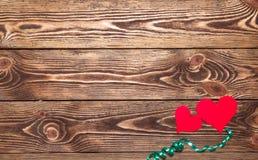 Ferie-/romantiker-/bröllop-/valentindagbakgrund med två pappers- hjärtor och band Arkivfoto