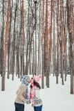 Ferie-, vinter-, jul-, förälskelse- och folkbegrepp - lyckligt par som kysser i skog bland granträd i snö Fotografering för Bildbyråer