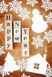 Feriebild för lyckligt nytt år med en hälsa text på träkuber och pappers- snöflingor och andra former arkivfoto