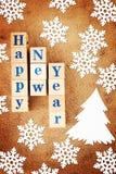 Feriebild för lyckligt nytt år med en hälsa text på träkuber och snöflingor och ett granträd arkivbild