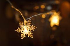 Feriegirlanden, den klara plast- snöflingan glöder med ett guld- ljus arkivfoton