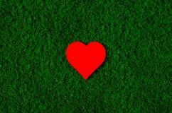 Feriekort: röd pappers- hjärta ligger på ett grönt gräs Fotografering för Bildbyråer