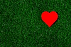 Feriekort: röd pappers- hjärta ligger på ett grönt gräs Royaltyfri Foto