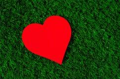 Feriekort: röd pappers- hjärta ligger på ett grönt gräs Arkivfoto