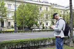 Ferien, Ferien, Ausflug: ein Tourist mit einem Rucksack, seiend auf Andrássy-Allee, legt einen gehenden Weg in einem Handy lizenzfreie stockfotos