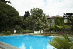 Ferien in den Tropen durch das Pool Die Sonne ` s Strahlen glänzen durch die Blätter von Bäumen Stockbilder