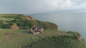 Ferien in der Natur, nette Firmenfreunde, die Spaß haben und Gitarre beim Stillstehen auf Picknick auf Freilicht am Hügel spielen stock footage