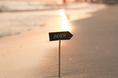 Ferien oder Feiertagskonzept - setzen Sie Zeichen und Sonnenuntergang auf den Strand Lizenzfreie Stockfotografie