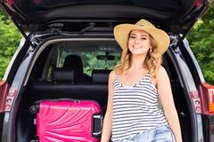 Ferien-, Reisekonzept - junge Frau bereit zur Reise an den Sommerferien mit Koffern und Auto Stockbild