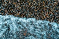 Ferien- und Reisekonzeptwelle bedeckt Pebble Beach an einem Sommertag, Seehintergrund lizenzfreie stockbilder