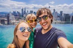 Ferien und Technologie Gl?ckliche Familie mit dem Kind, das zusammen selfie nahe Swimmingpool mit Panoramablicken von nimmt lizenzfreie stockfotografie