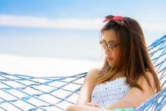Ferienfrau, die auf Strand in der Hängematte auf Sommer sich entspannt Stockfoto