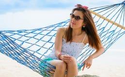 Ferienfrau, die auf Strand in der Hängematte auf Sommer sich entspannt Lizenzfreie Stockfotografie