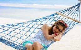 Ferienfrau, die auf Strand in der Hängematte auf Sommer sich entspannt Lizenzfreie Stockfotos