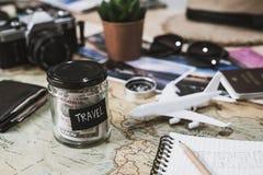 Feriengeldeinsparung in einem Glas mit Kamera auf Karte lizenzfreies stockbild