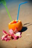 Ferienkonzept - Orange mit coctail Stroh und exotischen Blumen auf dem Strand Lizenzfreies Stockfoto